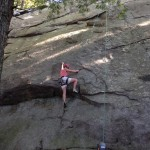Laura Alexander balancing up and over Slabs Overhang (5.7), at Pawtuckaway State Park, NH.